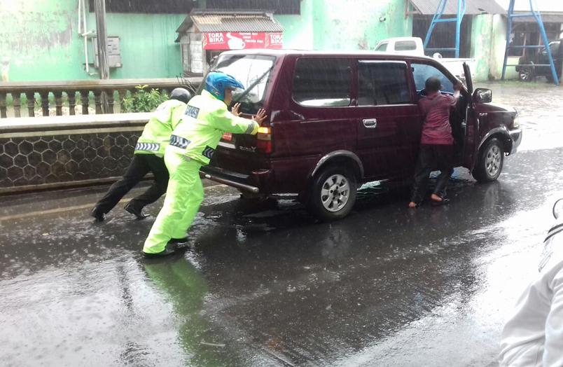 Tak Peduli Diguyur Hujan, Dua Polantas Ini Dorong Mobil Mogok