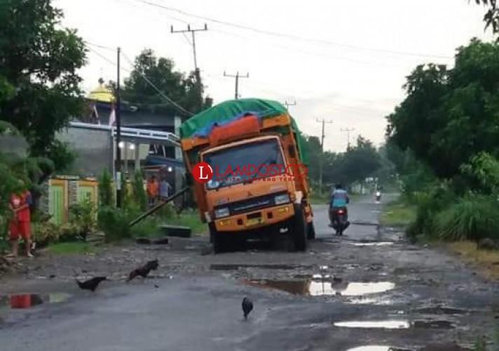 Fuso Muatan Gabah Amblas di Jalan Berlubang Poros Palas
