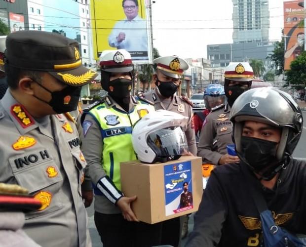 Polresta Bandar Lampung Bagi-bagi Sembako dan Helm di Tugu Adipura