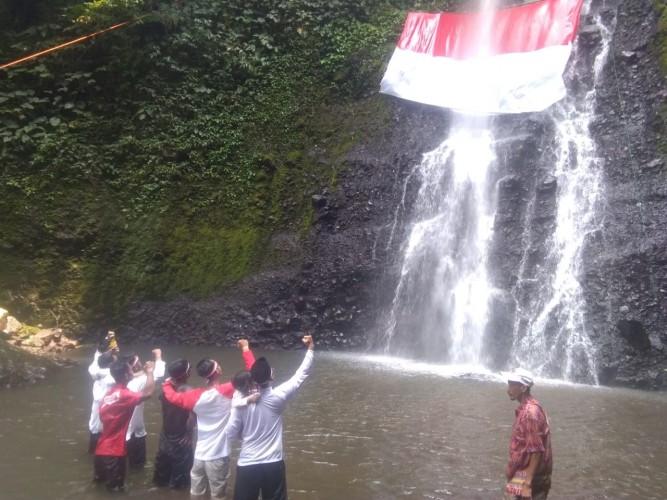 Unik, Tiga Ormas Kibarkan Bendera Merah Putih di Air Terjun