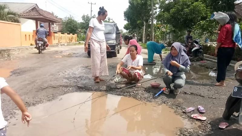 Warga Sukaraja Ramai-ramai Mancing di Kubangan Jalan